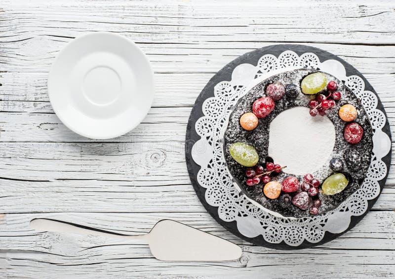 bolo da baga do chocolate na placa sobre o fundo de madeira branco foto de stock