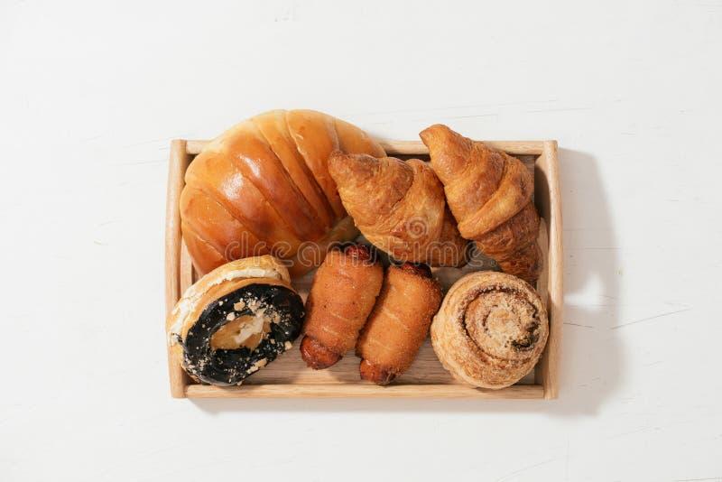 Bolo da filhós da amêndoa, croissant, bolo de caranguejo, bolo do rolo macio com a salsicha posta sobre a placa de madeira, foco  fotos de stock