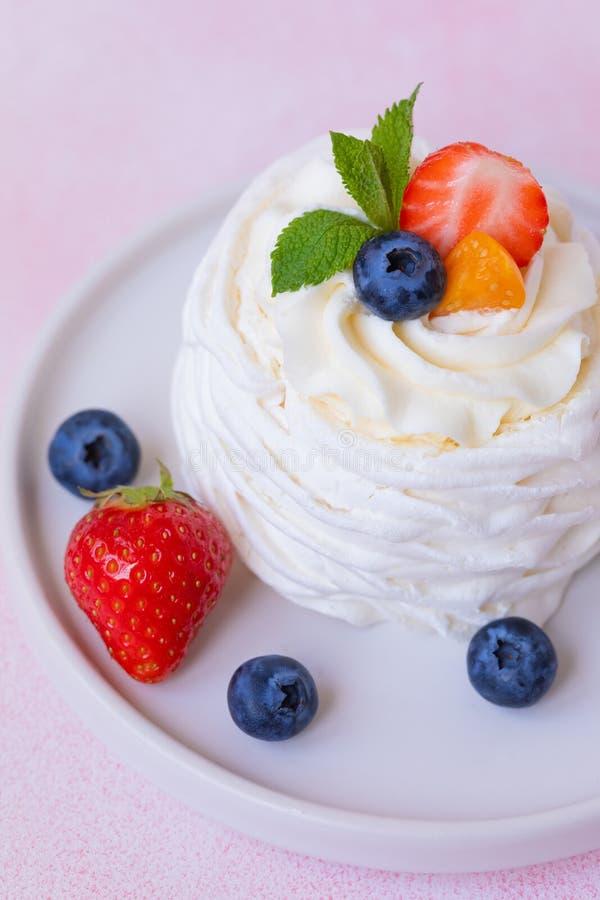 Bolo da merengue, do Pavlova com morangos, mirtilos e hortelã foto de stock