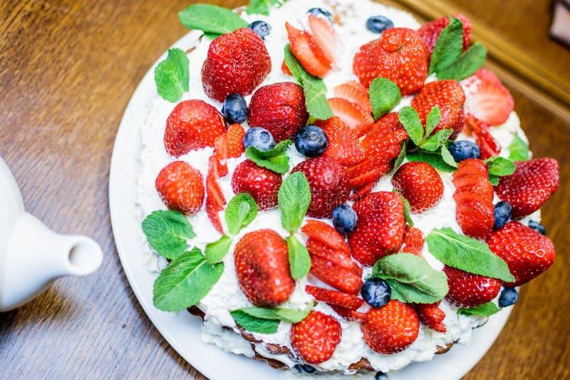 Bolo da morango com os mirtilos no bolo leavesStrawberry do creme e da hortelã nas folhas do creme e de hortelã na tabela em uma  imagem de stock royalty free