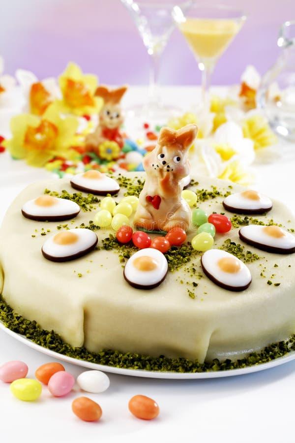 Bolo da Páscoa, bolo do maçapão com pistache, estatueta do coelhinho da Páscoa e fundente imagem de stock