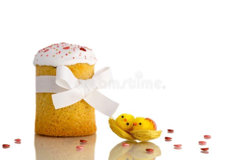 Bolo da Páscoa com os dois pintainhos amarelos e a fita branca isolados no fundo branco imagem de stock royalty free