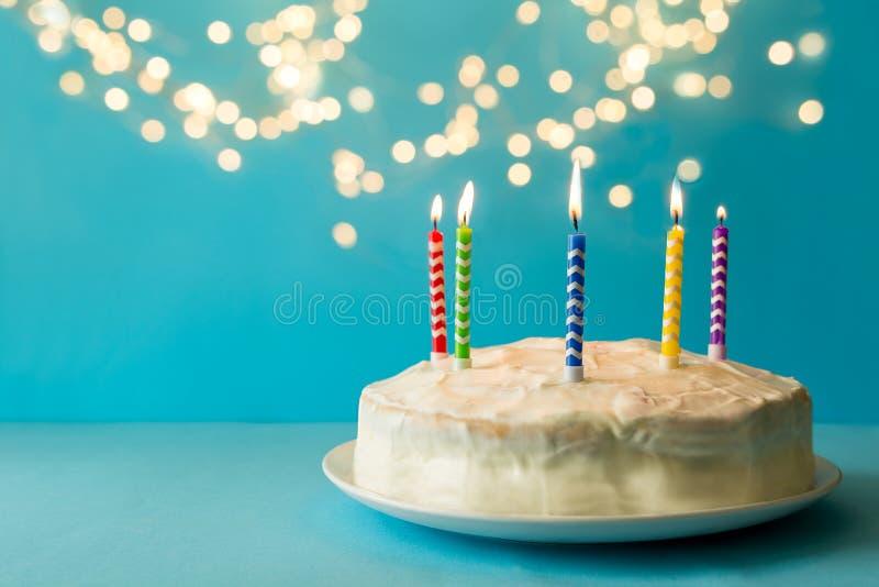 Bolo de aniversário branco com velas coloridas no fundo azul contra luz defocused Conceito da celebração do feriado Copie o espaç imagens de stock royalty free