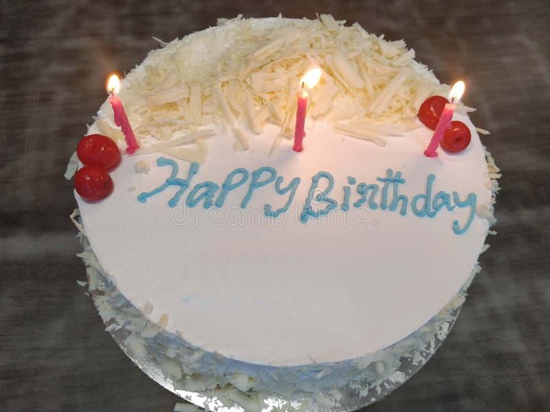 Bolo de aniversário branco com velas iluminadas imagem de stock