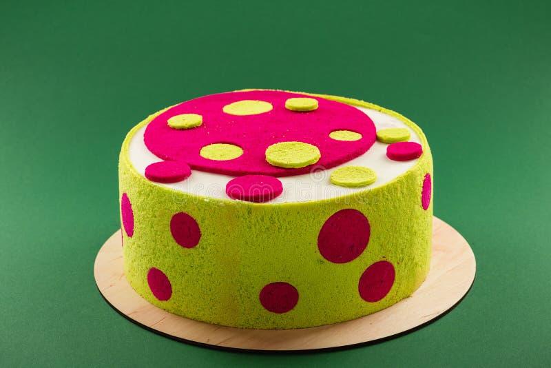 Bolo de aniversário colorido brilhante com os pontos verdes e cor-de-rosa fotografia de stock