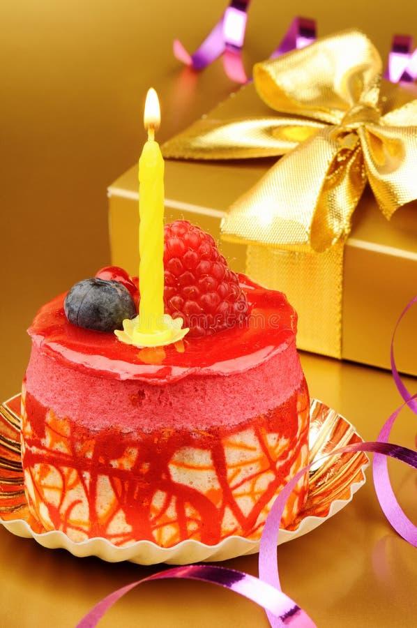 Bolo de aniversário colorido com vela imagens de stock royalty free