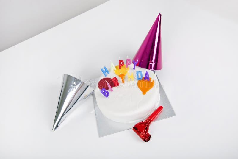Bolo de aniversário com chapéus do partido e noisemaker na tabela imagens de stock