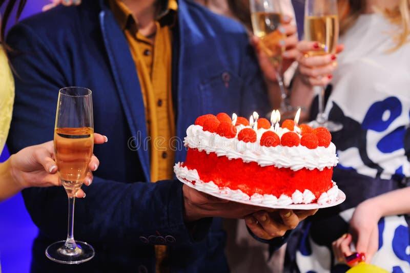 Bolo de aniversário com velas e um vidro do close up do champanhe imagem de stock