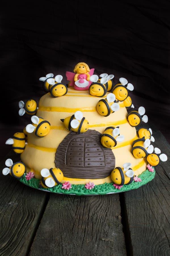 Bolo de aniversário das crianças na forma de uma colmeia com abelhas fotografia de stock