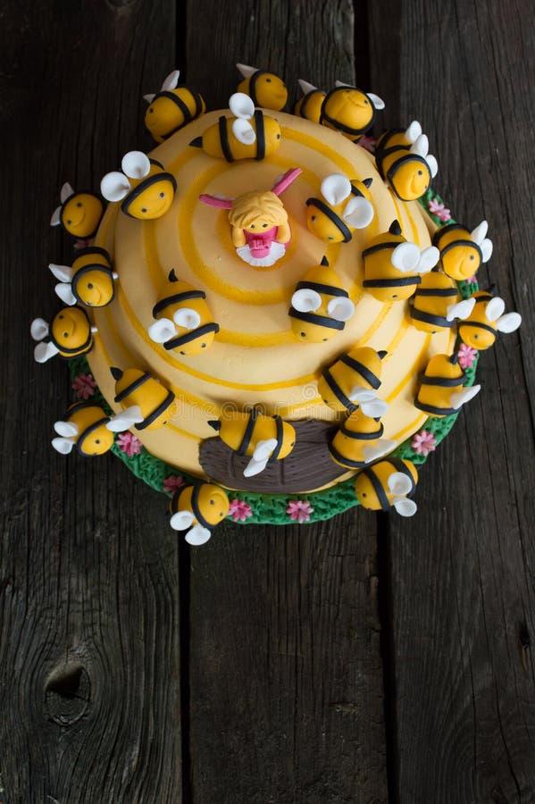 Bolo de aniversário das crianças na forma de uma colmeia com abelhas foto de stock
