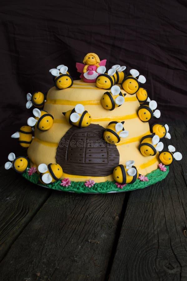 Bolo de aniversário das crianças na forma de uma colmeia com abelhas imagens de stock