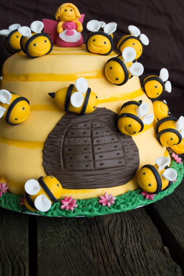 Bolo de aniversário das crianças na forma de uma colmeia com abelhas imagem de stock royalty free