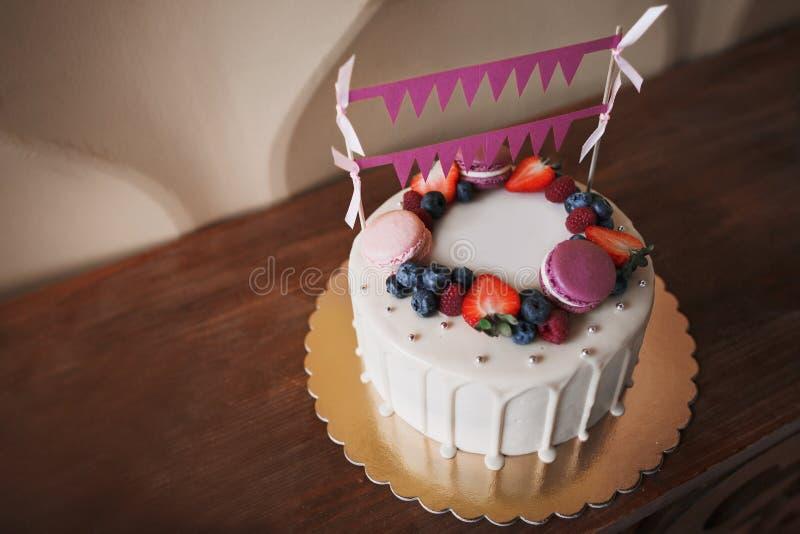 Bolo de aniversário do ` s das crianças No bolo há bagas da framboesa, mirtilos e bolinhos de amêndoa das morangos, os roxos e os fotografia de stock royalty free