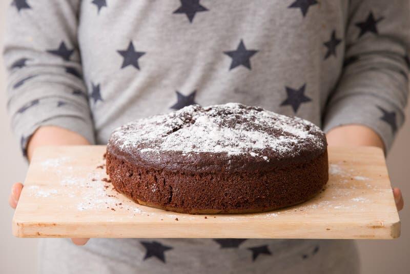 Bolo de aniversário escuro caseiro do chocolate com creme, pedaços de chocolate em sua parte superior Bolo com pó do açúcar branc imagens de stock