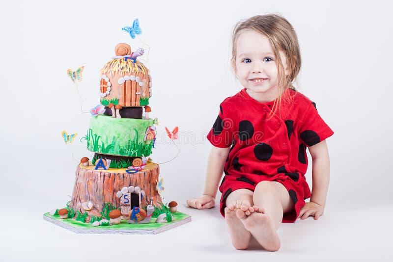 Bolo de aniversário extravagante e bonito perto da criança pequena imagens de stock royalty free
