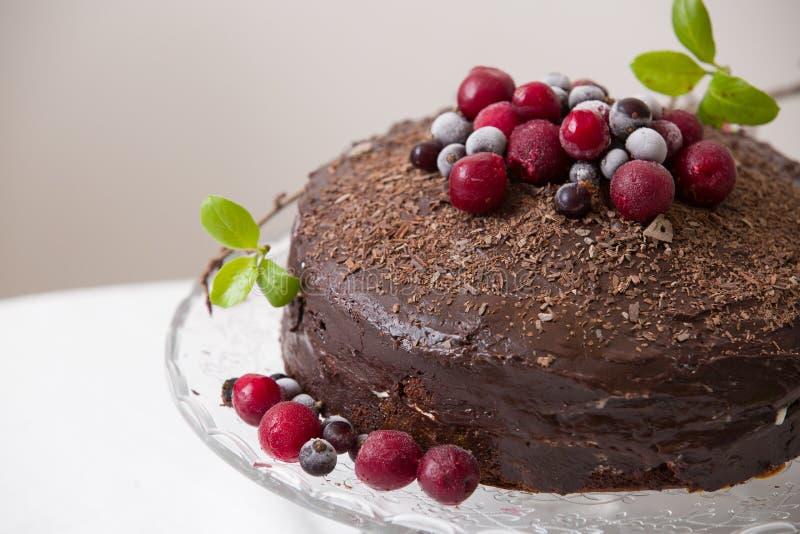 Bolo de aniversário fresco caseiro do chocolate com as bagas e as microplaquetas congeladas orgânicas e folhas da mola do freash  foto de stock royalty free
