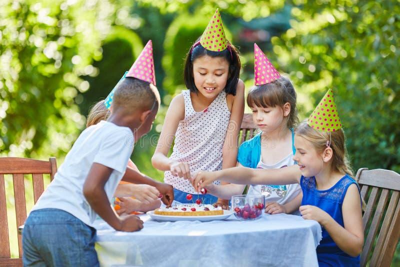 Bolo de aniversário no partido das crianças fotos de stock royalty free