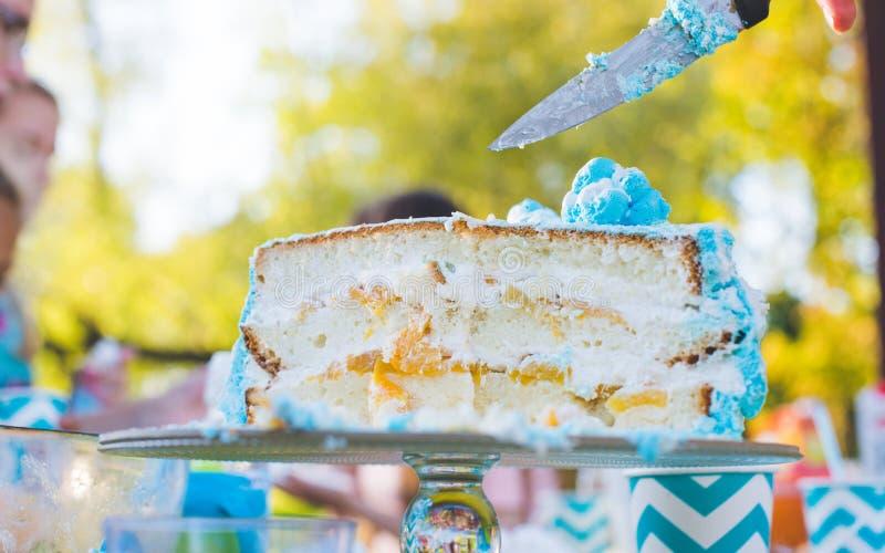 Bolo de aniversário para o aniversário Uma parte já cortou A faca corta o bolo Piquenique no parque em um dia ensolarado Azul do  foto de stock