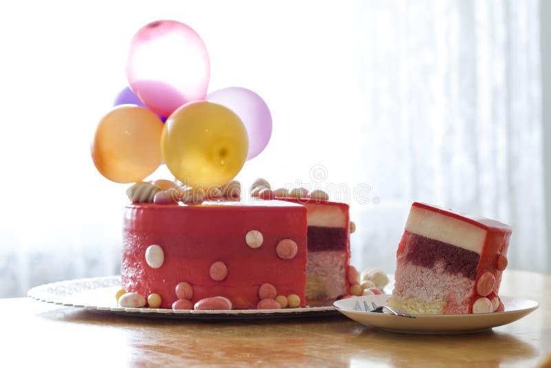 Bolo de aniversário vermelho caseiro com baloons do ar Fatia de um velv vermelho fotografia de stock royalty free