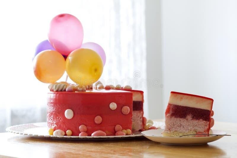 Bolo de aniversário vermelho caseiro com baloons do ar Fatia de um velv vermelho imagens de stock