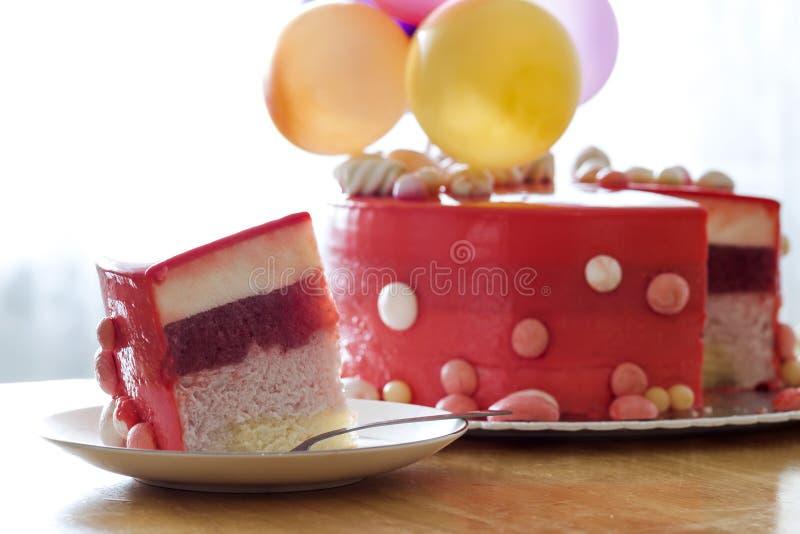 Bolo de aniversário vermelho caseiro com baloons do ar Fatia de um velv vermelho imagens de stock royalty free