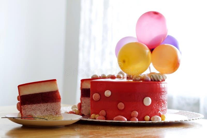 Bolo de aniversário vermelho caseiro com baloons do ar Fatia de um velv vermelho fotos de stock