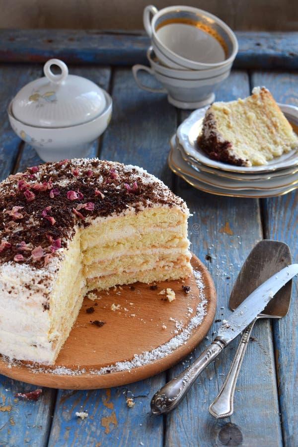 Bolo de camada delicioso do coco - biscoito e creme no creme do coco, decorado com chocolate raspado e as pétalas cor-de-rosa cri fotos de stock