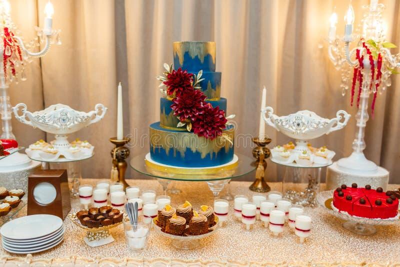 Bolo de casamento azul decorado estar das flores da tabela festiva com desertos, tartlet da morango e queques casamento fotos de stock royalty free