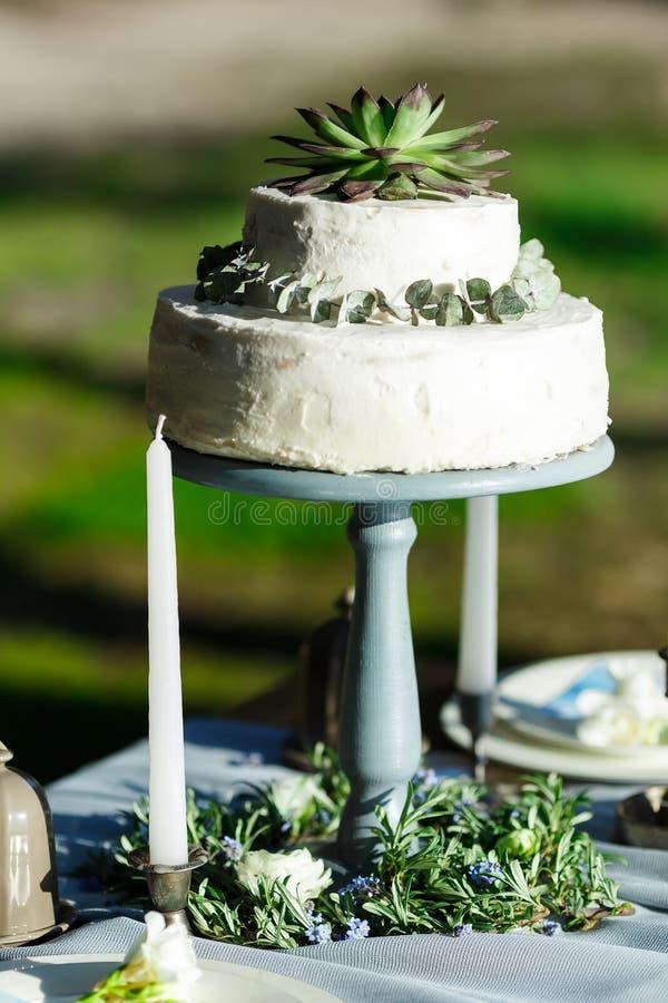 Bolo de casamento branco bonito com as flores exteriores fotos de stock royalty free