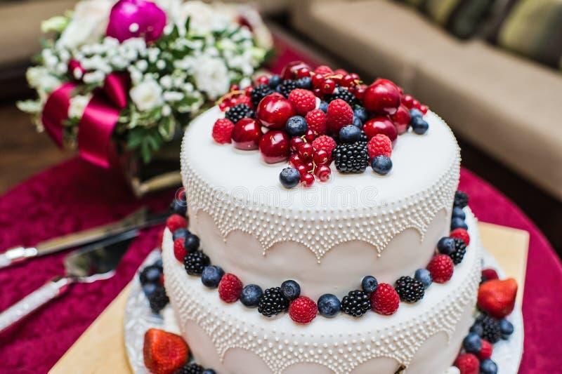 Bolo de casamento clássico com framboesas, morangos, amoras-pretas e mirtilos foto de stock