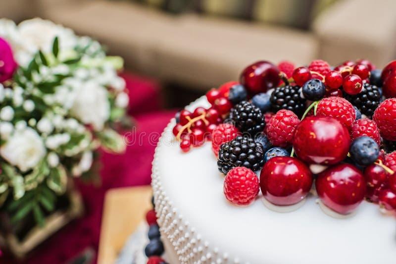 Bolo de casamento cl?ssico com framboesas, morangos, amoras-pretas e mirtilos imagens de stock