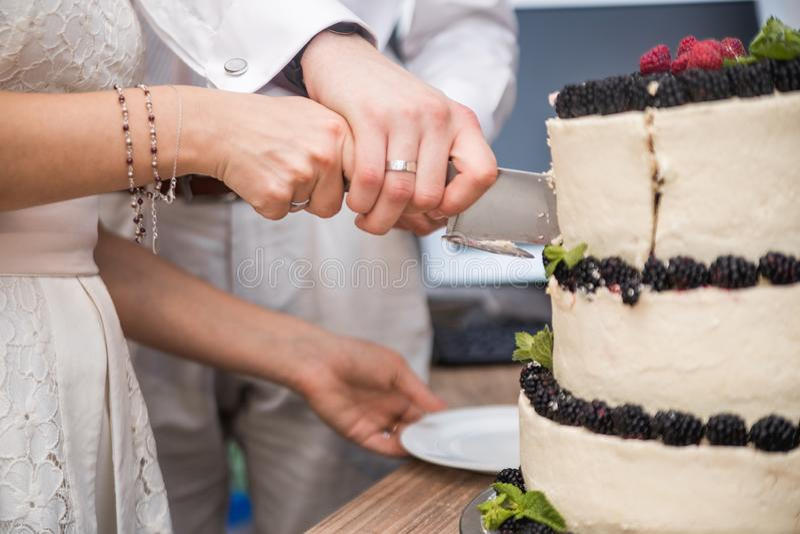 Bolo de casamento com as bagas na tabela de madeira Os noivos cortaram o bolo doce no banquete no restaurante foto de stock royalty free