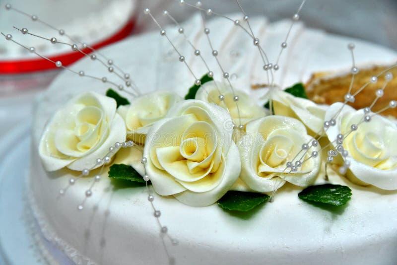 Bolo de casamento delicioso bonito decorado com os bolos na forma de rosas vermelhas e brancas foto de stock royalty free