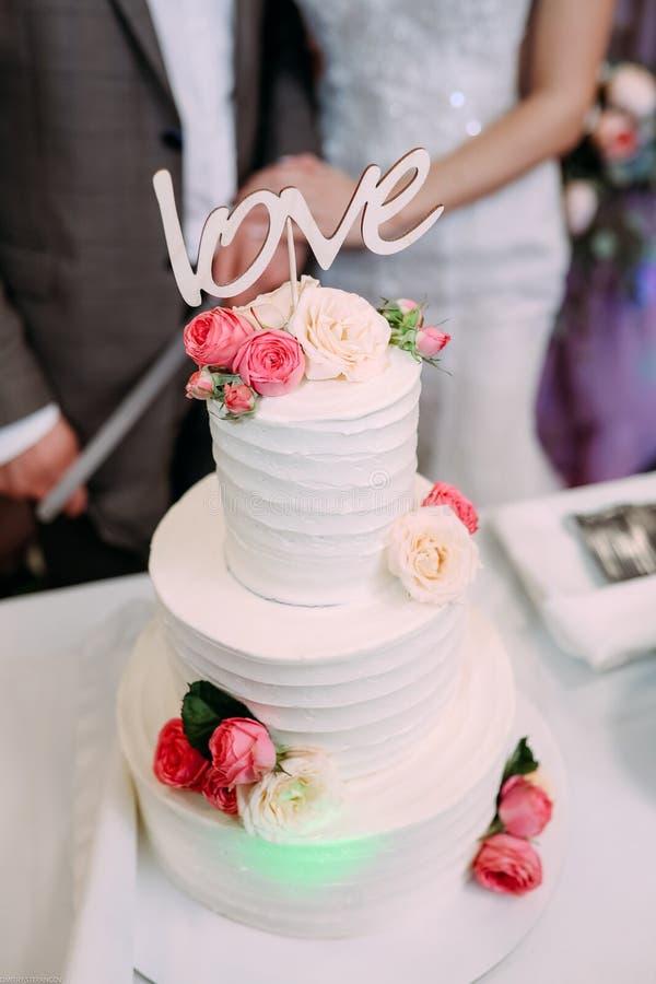 Bolo de casamento multi-estratificado bonito com o amor da inscrição fotos de stock royalty free