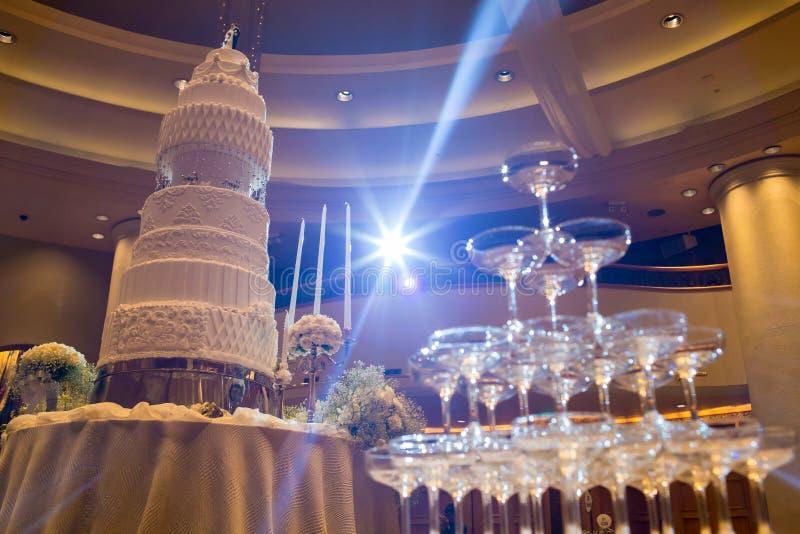 bolo de casamento na flor perto da pirâmide do vidro de Champagne fotografia de stock