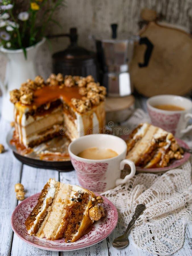 Bolo de cenoura com o interior salgado do caramelo e do bolo de queijo, decorado com pipoca e caramelo Uma fatia de bolo com uma  fotografia de stock