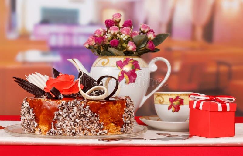 Bolo de chocolate, chá do copo, presente e rosas do ramalhete na cozinha fotografia de stock royalty free