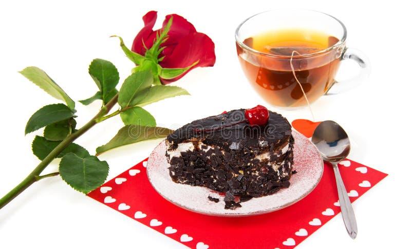 Bolo de chocolate, chá quente e rosa do vermelho foto de stock royalty free