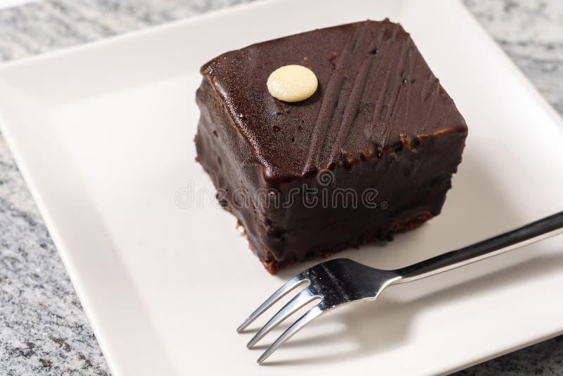 Bolo de chocolate com as cerejas servidas na placa branca quadrada imagens de stock royalty free