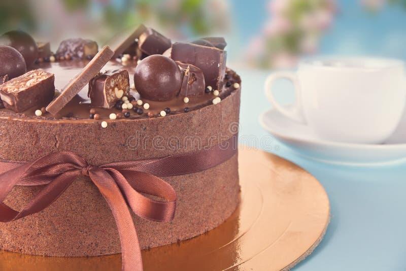 Bolo de chocolate com doces e fita em uma tabela azul fotos de stock