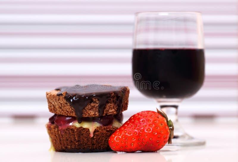 Bolo de chocolate com uma morango e um vidro do vinho tinto imagem de stock