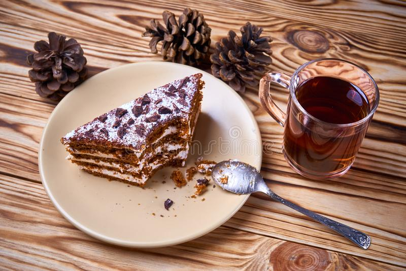 Bolo de chocolate com uma parte cortada em uma placa, copo do chá preto quente fotos de stock