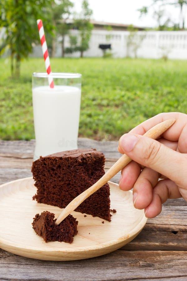 Bolo de chocolate de madeira da colheita da forquilha do uso da mão da mulher imagens de stock royalty free