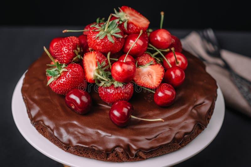 Bolo de chocolate de Tuscan com morangos e cerejas imagem de stock royalty free