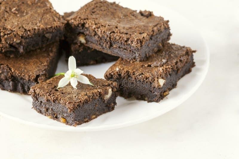 Bolo de chocolate delicioso em uma placa branca decorada com uma flor Cozimento caseiro Torta americana tradicional Torta da noz- foto de stock