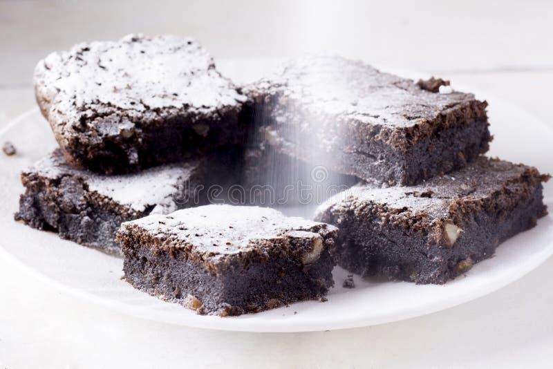Bolo de chocolate delicioso em uma placa branca, espanada com a??car de crosta de gelo Cozimento caseiro Torta americana tradicio imagem de stock