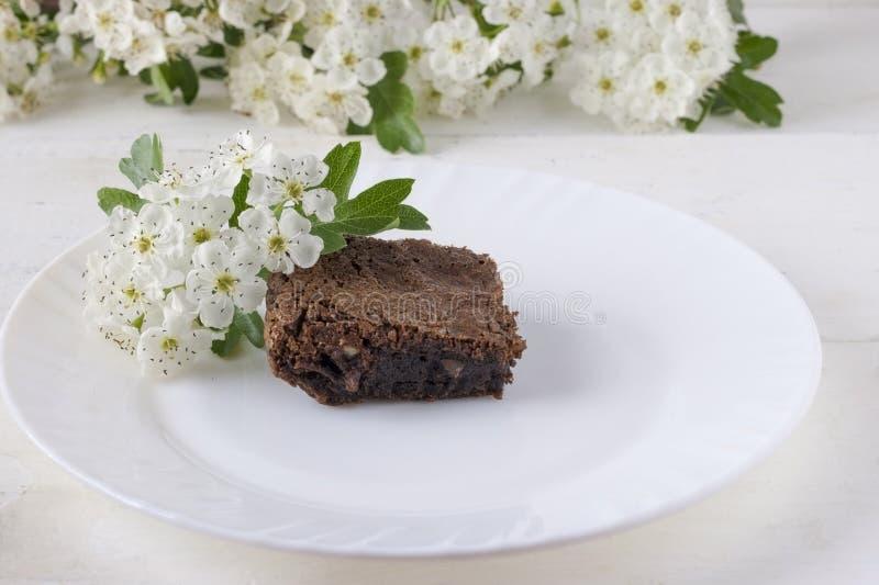 Bolo de chocolate delicioso em uma placa branca em uma tabela branca Pastelarias caseiros Torta americana tradicional Copie o esp fotografia de stock