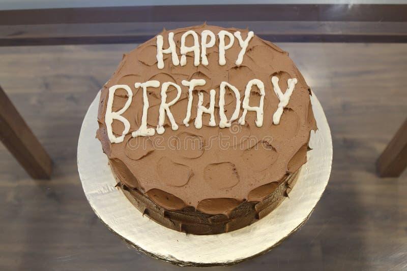Bolo de chocolate no texto médio do feliz aniversario marrom, no branco fotografia de stock royalty free