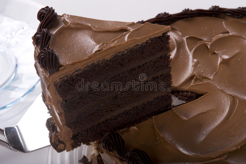 Bolo de chocolate que está sendo cortado imagens de stock royalty free