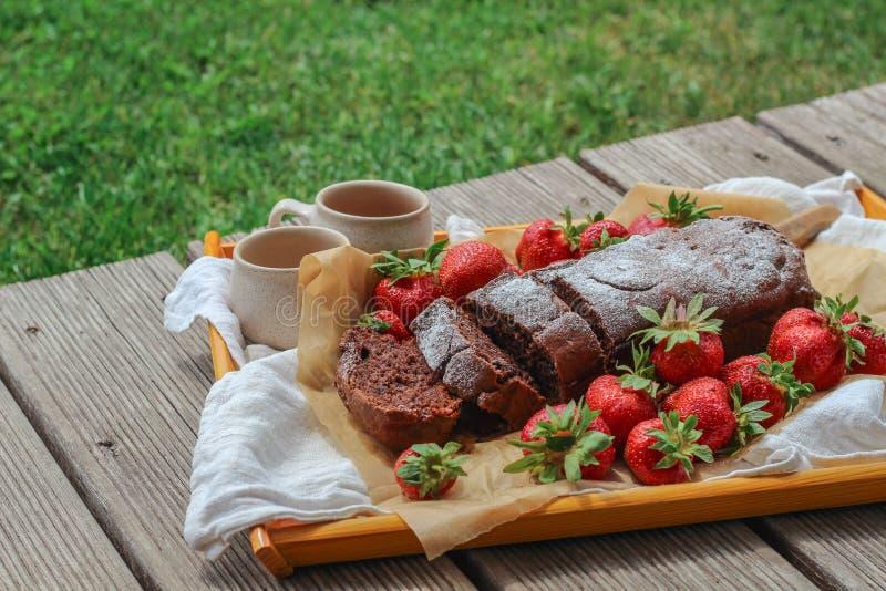 Bolo de chocolate recentemente cozido com as morangos trazidas fora ao terraço fotos de stock royalty free
